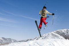Esquiador da neve que salta sobre o céu azul foto de stock royalty free