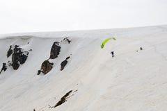 Esquiador de la cometa que vuela del canto de la montaña Fotografía de archivo