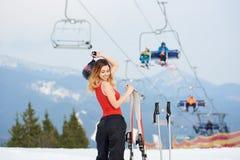 Esquiador de la mujer en el top de la colina nevosa con los esquís en la estación de esquí Imágenes de archivo libres de regalías
