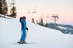 Esquiador de la mujer en la montaña de la nieve que muestra los pulgares para arriba del bueno Foto de archivo libre de regalías