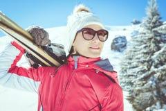 Esquiador de la mujer joven que sostiene los esquís que se colocan en montañas del invierno imagen de archivo libre de regalías