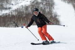 Esquiador de la mujer joven que viene abajo el esquí de la montaña en un día soleado Imagen de archivo