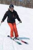Esquiador de la mujer joven que viene abajo el esquí de una montaña en un soleado Imagen de archivo libre de regalías