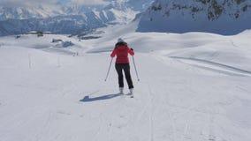 Esquiador de la mujer que esquía abajo de cuesta de montaña ella que empuja los palillos Sit Down To Gain Speed almacen de metraje de vídeo