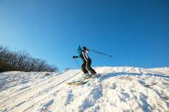 Esquiador de la mujer que esquía cuesta abajo en el bosque del invierno Foto de archivo libre de regalías