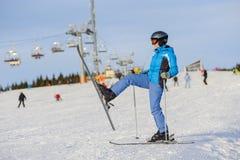 Esquiador de la mujer que esquía cuesta abajo en la estación de esquí contra el funicular Imagenes de archivo