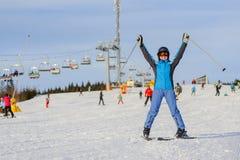 Esquiador de la mujer que esquía cuesta abajo en la estación de esquí contra el funicular Imagen de archivo libre de regalías