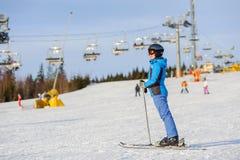 Esquiador de la mujer que esquía cuesta abajo en la estación de esquí contra el funicular Fotos de archivo