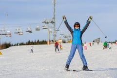 Esquiador de la mujer que esquía cuesta abajo en la estación de esquí contra el funicular Fotografía de archivo