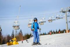 Esquiador de la mujer que esquía cuesta abajo en la estación de esquí contra el funicular Foto de archivo libre de regalías