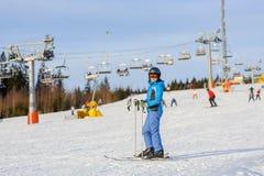 Esquiador de la mujer que esquía cuesta abajo en la estación de esquí contra el funicular Imagen de archivo