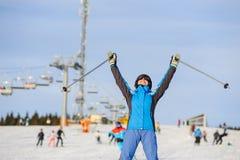 Esquiador de la mujer que esquía cuesta abajo en la estación de esquí contra el funicular Imágenes de archivo libres de regalías