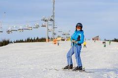 Esquiador de la mujer que esquía cuesta abajo en la estación de esquí contra el funicular Fotos de archivo libres de regalías
