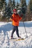 Esquiador de sexo femenino del país cruzado en bosque en DA asoleada Imagenes de archivo