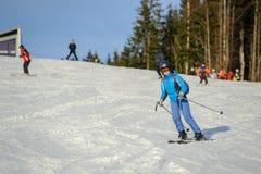Esquiador de sexo femenino que esquía cuesta abajo en la estación de esquí Fotografía de archivo libre de regalías