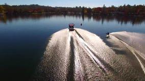 Esquiador de sexo masculino profesional del agua que se desliza en agua azul tranquila del lago en el paisaje soleado de Forest P metrajes