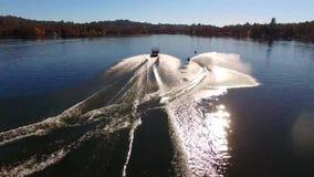 Esquiador de sexo masculino profesional del agua que se desliza en agua azul tranquila del lago en el paisaje soleado de Forest P almacen de metraje de vídeo