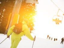 Esquiador de sexo masculino que esquía cuesta abajo en la estación de esquí contra el funicular Fotografía de archivo
