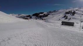 Esquiador de viagem nas trilhas do snowcat nas montanhas na inclinação filme