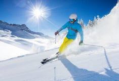 Esquiador del hombre joven que corre abajo de la cuesta en montañas alpinas Fotos de archivo libres de regalías