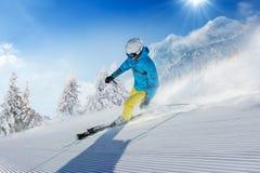 Esquiador del hombre joven que corre abajo de la cuesta en montañas alpinas Imagen de archivo