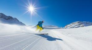 Esquiador del hombre joven que corre abajo de la cuesta en montañas alpinas Fotografía de archivo libre de regalías