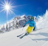 Esquiador del hombre joven que corre abajo de la cuesta en montañas alpinas Imagen de archivo libre de regalías