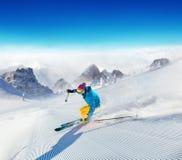 Esquiador del hombre joven que corre abajo de la cuesta en montañas alpinas Fotos de archivo