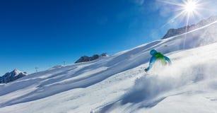 Esquiador del hombre joven que corre cuesta abajo en nieve del polvo Imagen de archivo libre de regalías