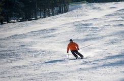 Esquiador del hombre que esquía cuesta abajo en la estación de esquí Imagenes de archivo