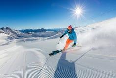 Esquiador do homem novo que corre abaixo da inclinação em montanhas alpinas Fotografia de Stock