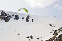 Esquiador do papagaio que voa fora do cume da montanha Foto de Stock Royalty Free