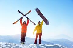 Esquiador e snowboarder ativos contra montanhas Foto de Stock Royalty Free