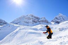 Esquiador en el medio de las montañas que esquía abajo de la colina Foto de archivo libre de regalías
