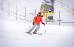 Esquiador en la chaqueta roja que va abajo de la colina rápidamente Foto de archivo libre de regalías