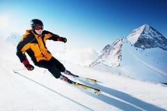 Esquiador en montañas, piste preparado y día asoleado foto de archivo