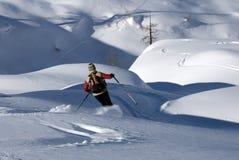 Esquiador en una cuesta en nieve del polvo Foto de archivo