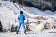 Esquiador fêmea em uma inclinação do esqui em um dia ensolarado Fotos de Stock Royalty Free