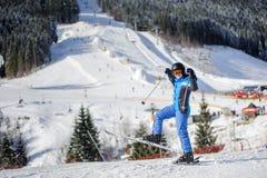 Esquiador fêmea em uma inclinação do esqui em um dia ensolarado Imagens de Stock Royalty Free