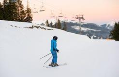 Esquiador fêmea no meio da inclinação do esqui contra elevadores de esqui Fotografia de Stock Royalty Free