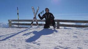 Esquiador feliz de sorriso na montanha que mostra o polegar APROVADO do gesto acima e os braços dos aumentos vídeos de arquivo