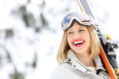 Esquiador feliz que sostiene los esquís que miran el lado Imagenes de archivo