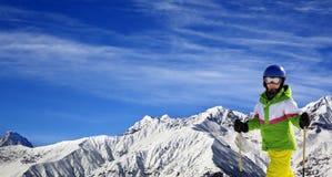 Esquiador joven con en las montañas de la nieve en el día de invierno del sol Fotos de archivo
