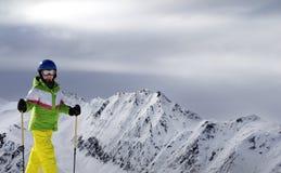 Esquiador joven con los polos de esquí en montañas de la luz del sol y gris nublado Fotografía de archivo