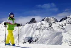 Esquiador joven con los polos de esquí en montañas de la nieve en el día de invierno del sol Fotos de archivo libres de regalías
