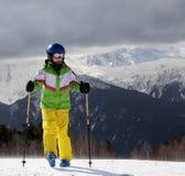 Esquiador joven con los polos de esquí en montañas del sol y cielo gris antes Fotos de archivo libres de regalías