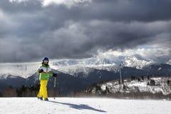 Esquiador joven con los polos de esquí en montañas del sol y cielo gris nublado Fotos de archivo libres de regalías