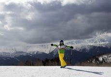 Esquiador joven feliz con los polos de esquí en montañas del sol y gra nublado Fotos de archivo