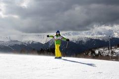 Esquiador joven feliz con los polos de esquí en montañas del sol y gra nublado Imágenes de archivo libres de regalías
