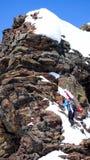 Esquiador masculino do país traseiro que escala a uma cimeira rochosa exposta com seus esquis prendidos com correias a sua trouxa Imagens de Stock